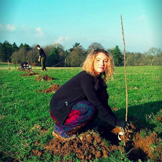 Young woman planting tree on Huxhams Cross Farm on a sunny day