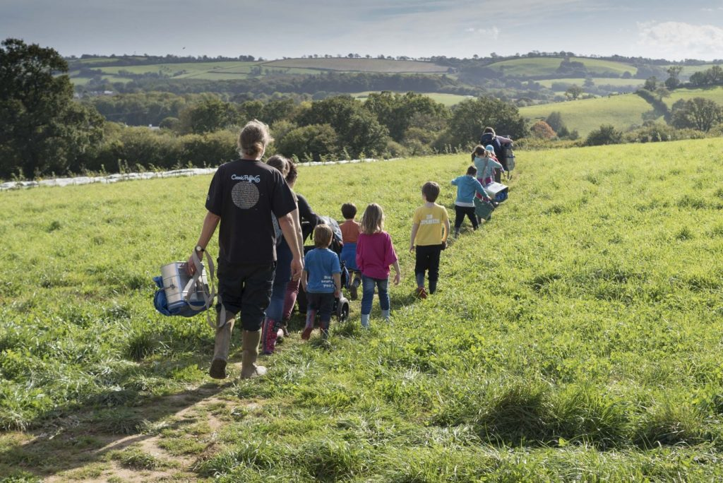Farm School make their way across a beautiful green field at Huxhams Cross Farm