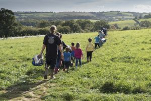 Children and adults in Farm School make their way across a beautiful green field at Huxhams Cross Farm
